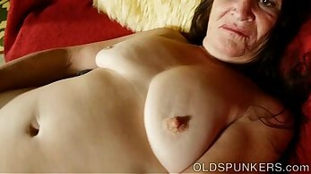 Brunette flashes her mature pussy outside on the grass